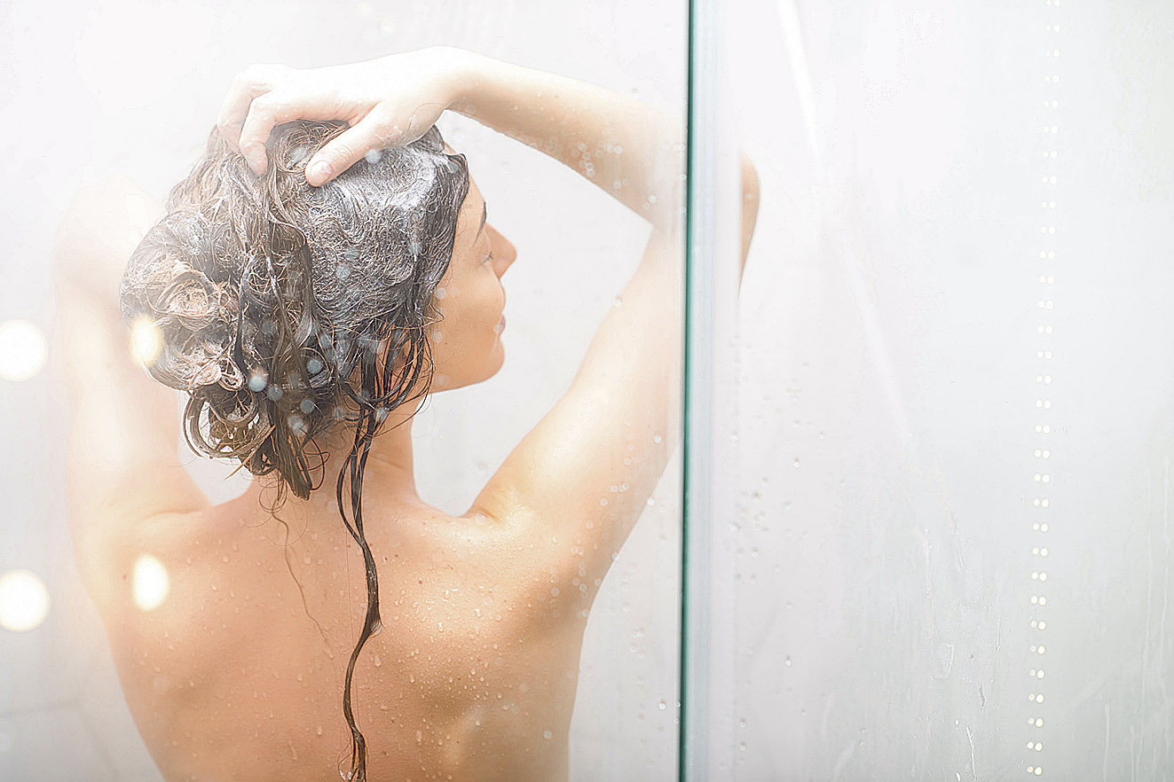 Eine Frau wäscht sich unter der Dusche die Haare. Thema: bakterielle Vaginose