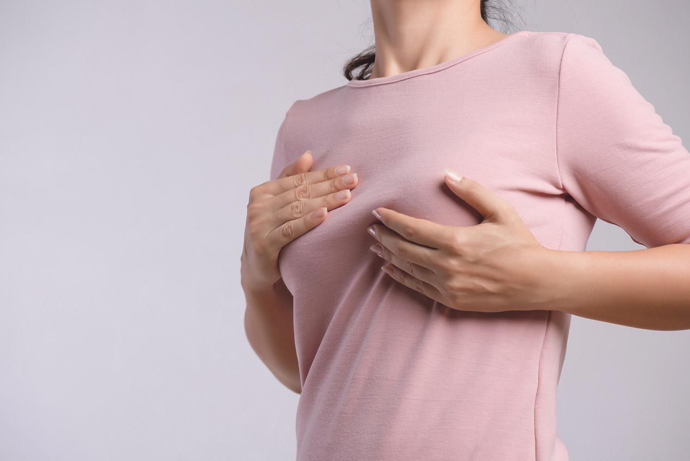 Eine Frau tastet ihre Brust über dem Shirt ab.