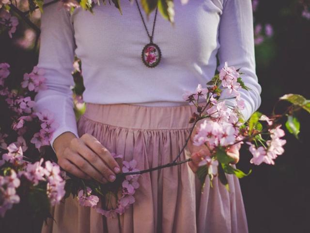 Detail: Eine Frau hält einen Ast mit Blüten in der Hand