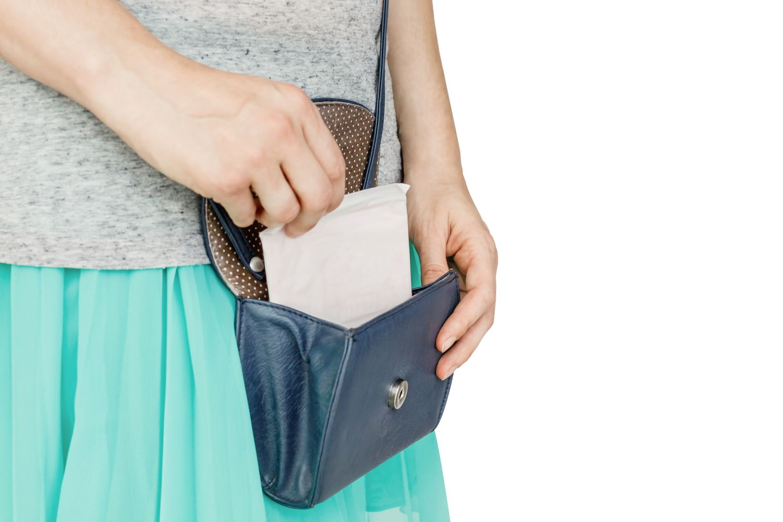 Eine Frau steckt eine Slipeinlage in ihre Handtasche