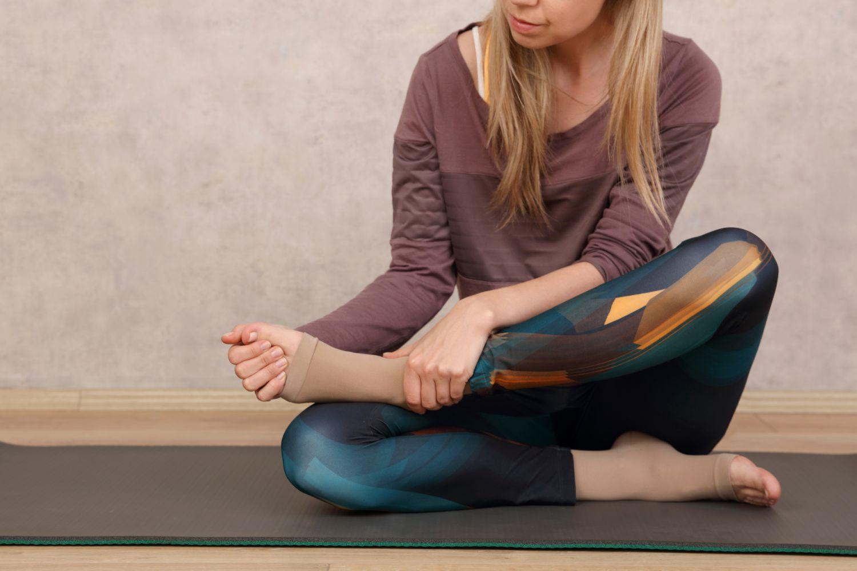 Yoga-Sportlerin sitzt auf einer Matte und zieht einen Kompressionsstrumpf an. Thema: Venenprobleme