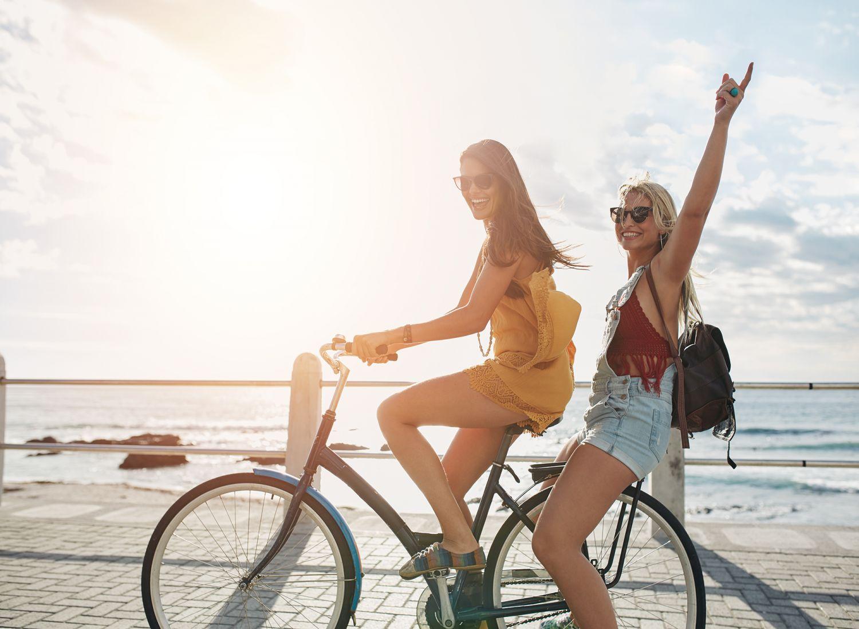 Zwei Frauen fahren Fahrrad auf einer Promenade am Meer