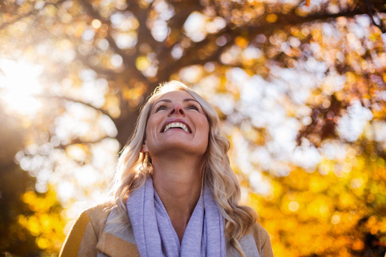 Eine Frau lächelt unter einem herbstlichen Baum. Thema: Wechseljahresbeschwerden