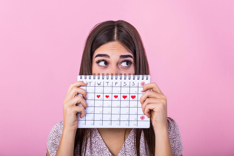 Frau, die sich schamhaft einen Kalender vors Gesicht hält