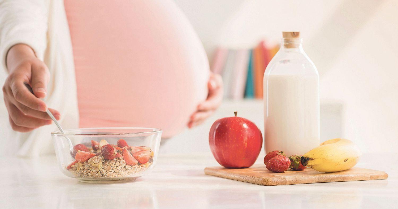 Eine schwangere Frau macht sich Müsli. Thema: Verstopfung