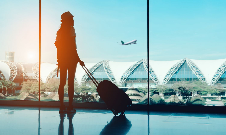 Reisende mit Koffer am Flughafen. Thema: Stressvermeidung