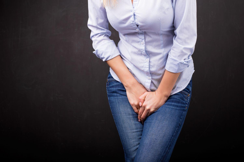 Eine Frau hält die Hände vor ihren Schritt. Thema: Blasenschwäche