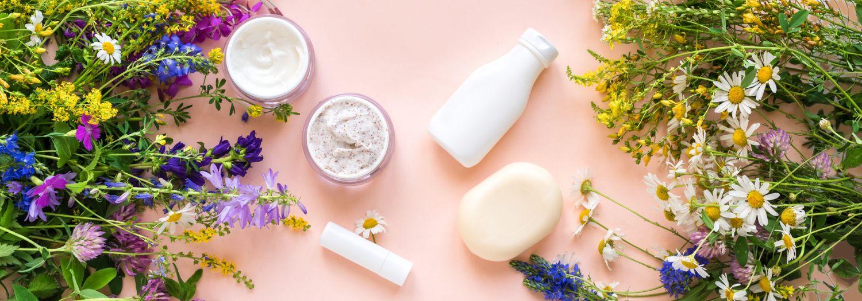 Kosmetik in Fläschchen und Döschen, umrandet von Blumen. Symbolbild Naturkosmetik