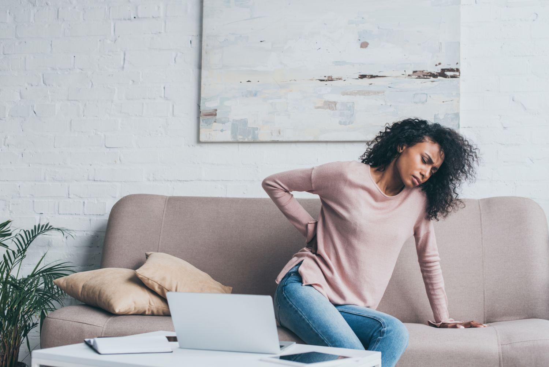 Eine Frau arbeitet von zuhause und hält sich den Rücken, weil sie Schmerzen hat.
