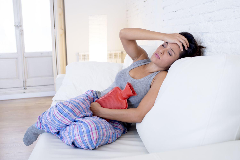 Eine Frau liegt mit Regelschmerzen auf der Couch. Endometriose kann eine schmerzhafte Angelegenheit sein