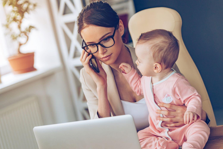 Arbeitende Frau mit Baby am Schreibtisch. Thema: Powerfrauen