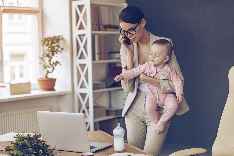 Eine arbeitstätige Mutter hat ihr Baby auf dem Arm. Thema: Frauengesundheit
