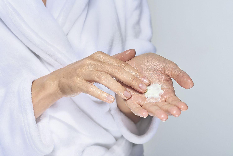Eine Frau cremt sich ihre Hände ein. Thema: Schuppenflechte