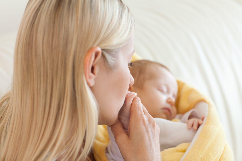 Eine Frau küsst ihr Baby. Thema: Frühgeburt durch bakterielle Vaginose