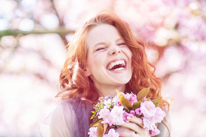Eine Frau hält Blumen in der Hand und lacht. Thema: Bio-Slipeinlagen