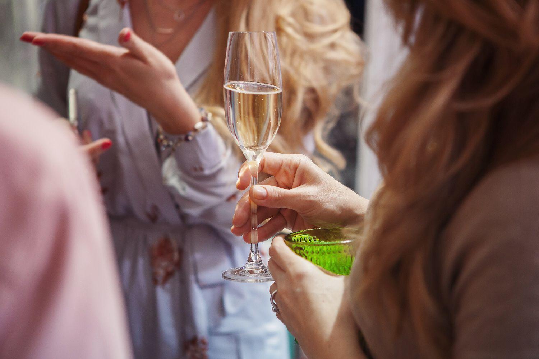 Eine Frau hält ein Sektglas. Thema Alkoholismus und Frauen