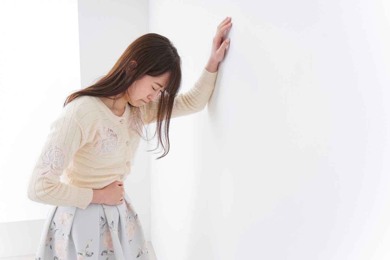 Eine Frau stützt sich vor Schmerz an einer Wand ab. Thema Endometriose