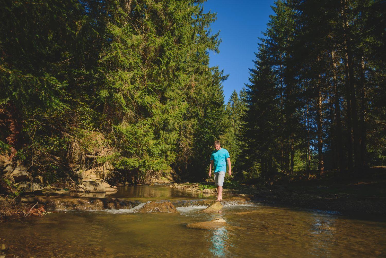 Mann watet barfuß durch einen Fluss im Wald.
