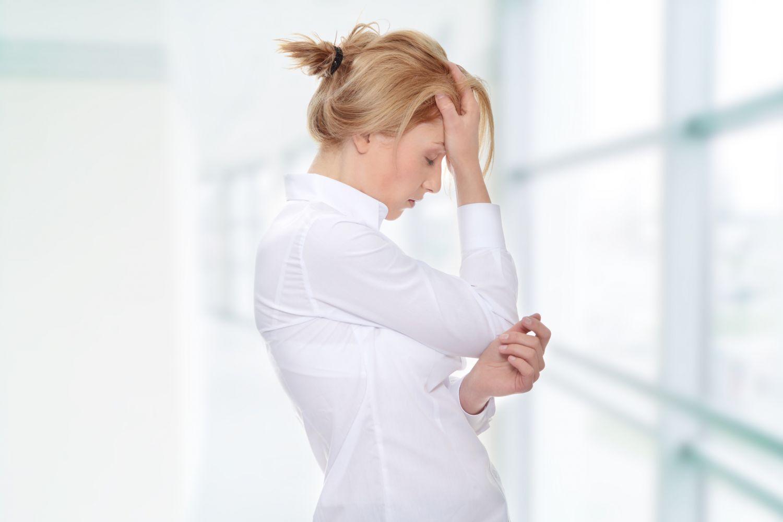 Eine Frau hält sich vor Schmerzen eine Hand an den Kopf. Thema: PMS