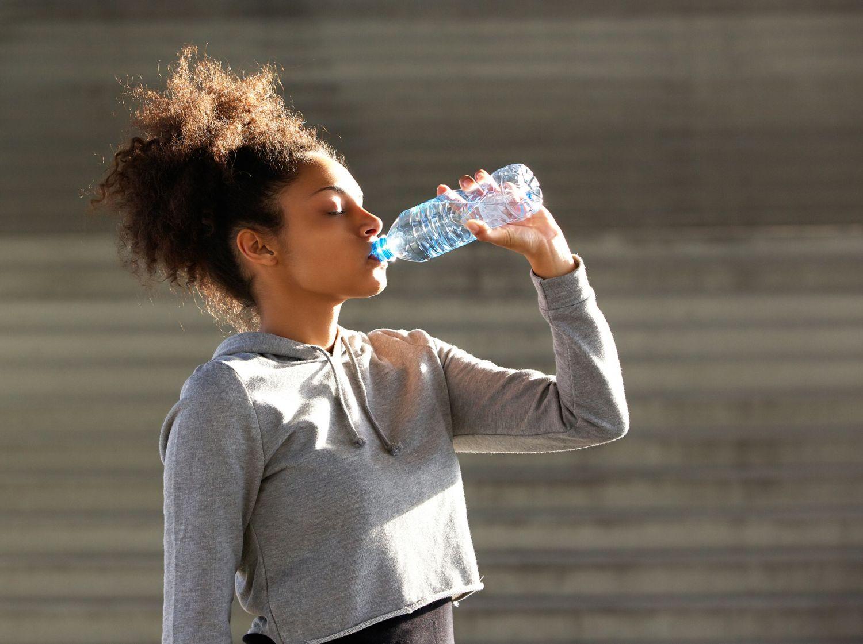 Eine Frau trinkt Wasser aus einer Plastikflasche. Thema: Alterungsprozess