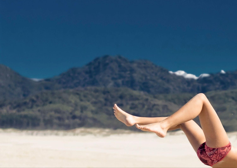 Eine Frau streckt am Strand ihre Beine von sich. Thema: Scheidenpilz