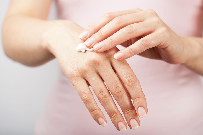 Eine Frau cremt ihre Hände ein. Thema: Hautjucken